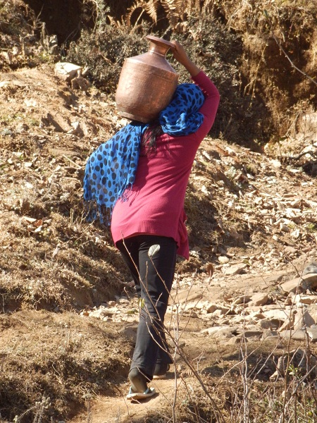 A nepali lady carrying a water jug in her shoulder