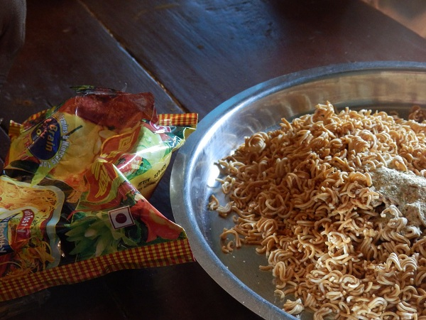 Dried noodles in a dish, next to empty packet