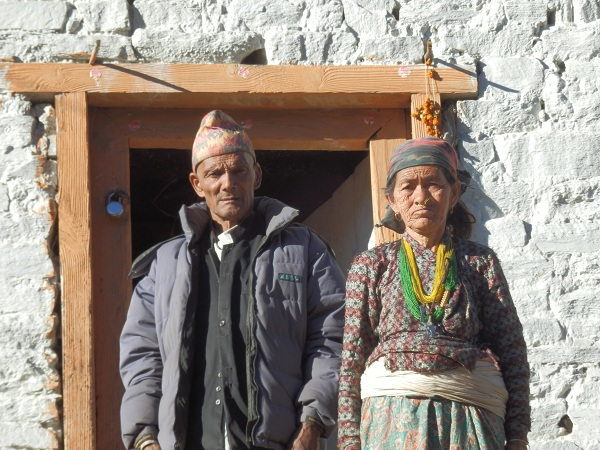 Nepali Man and Lady standing in front of their house