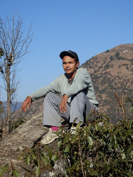 Nepal - my porter sitting on a rock