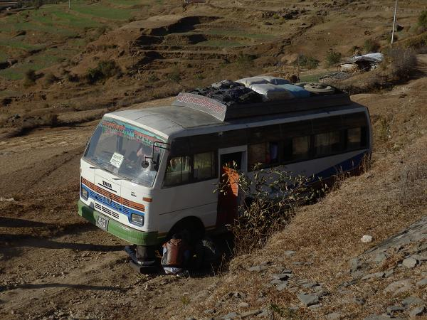Nepal - Bus driver fixing puncture on the side of the road