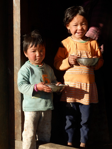 Two sherpa children standing in a doorway