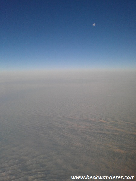 In an aeroplane looking down at snow clouds and moon in the distance