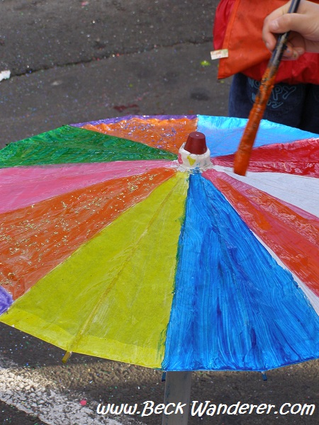 Children painting umbrellas very colourfully