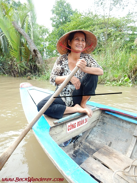 Lady rowing a traditional boat on the Mekong Delta
