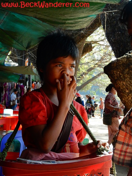 A little boy seller picking his nose at Angkor Wat markets, Cambodia