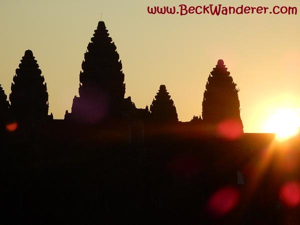 Sun coming up behind Angkor Wat temples
