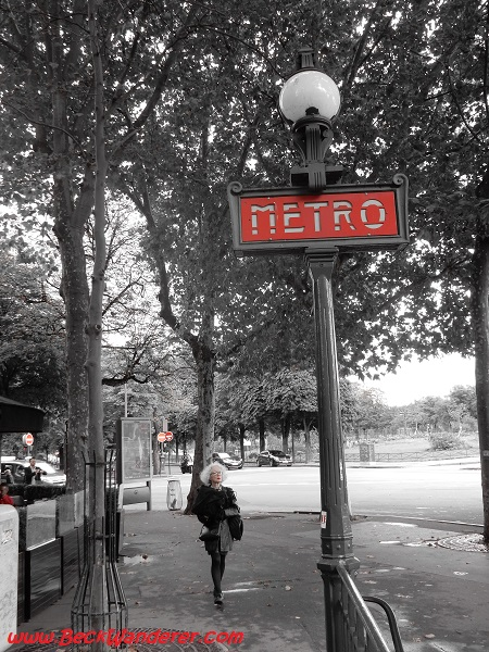 Black, white and red picture of lady walking next to metro sign