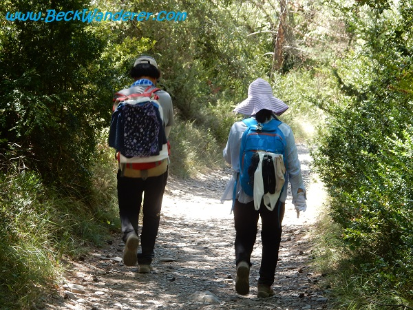 Two pilgrims with their clothes pinned to their ruck sacks
